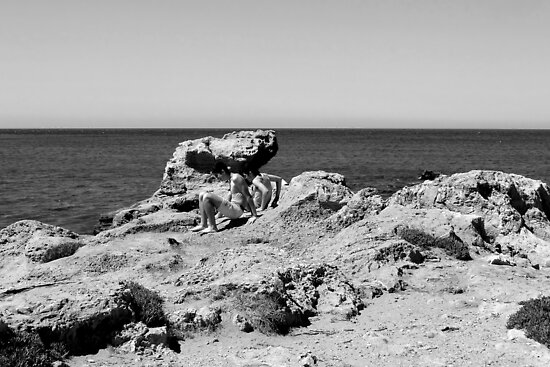 Boys climbing on rocks at Chania Beach, Crete, Greece by Susan Wellington