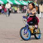 Little Korean Girl Learning to Ride a Bike by Christian Eccleston