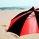 Red and Black Umbrella on the Beach with Footprints by Randall Nyhof