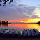 Sunrise with Canoes by Debbie  Maglothin