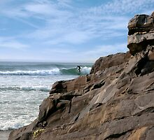 lone surfer near rocks by morrbyte