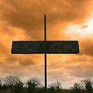 metal cross against a red stormy sky by morrbyte
