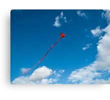 Flying red heart - shaped kyte on a clear blue sky Canvas Print