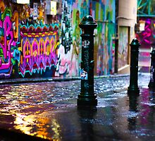 Bollards in a Rainy Graffiti Lane by jamjarphotos