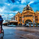 Cyclist looks at Flinders Street Station on a Wet Day by jamjarphotos