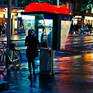 Girl on a public phone on a cold wet night by jamjarphotos