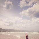 Girl Walking Along a Beach by jamjarphotos