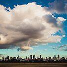 Enormous clouds dwarf a city skyline by jamjarphotos
