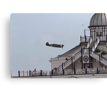 A spitfire flies over the pier at Eastbourne Canvas Print