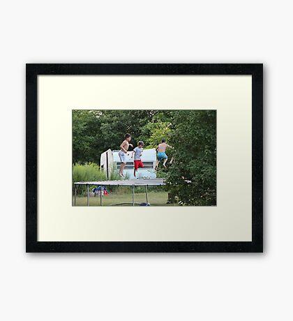 boys jumping on trampoline Framed Print