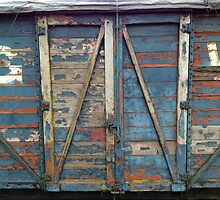 Railway boxcar or goods van with peeling blue paint. by Colin Tester