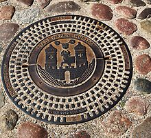 Decorative iron man-hole cover in old street in Waren (Müritz), Mecklenburg, Germany. by David A. L. Davies
