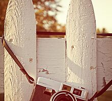 Vintage film camera on picket fence by Edward Fielding