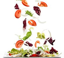 Salad with fresh vegetables falling on plate by Pablo Romero