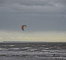 A Lone Kite Surfer Flying Across Stormy Seas by lynn carter