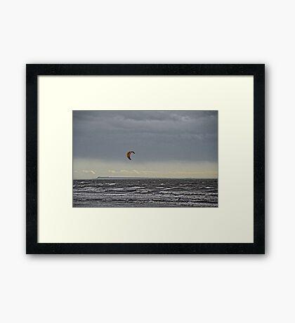 A Lone Kite Surfer Flying Across Stormy Seas Framed Print