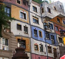 Front of a colourful building by Hundertwasser with a sign, Vienna by Ilan Cohen