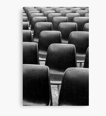 Plastic black chairs under rain Canvas Print