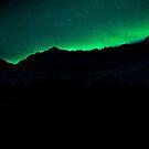 aurora borealis over mountain ridge by tara romasanta