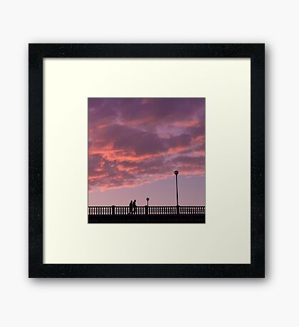 Two people walking on a bridge, in the evening Framed Print