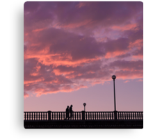 Two people walking on a bridge, in the evening Canvas Print