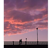 Two people walking on a bridge, in the evening Photographic Print