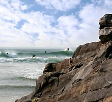 surfers near rocks by morrbyte