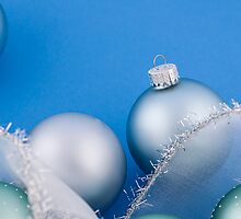 Christmas baubles on blue by Elena Elisseeva