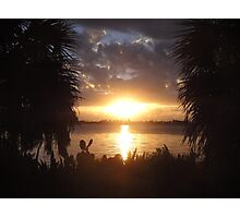 Sunset over water with plants around Photographic Print
