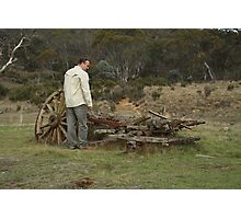 Man standing over wooden wagon relics Photographic Print