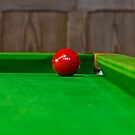 Red pool ball on a pool table by ashishagarwal74