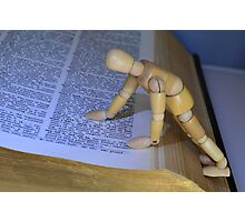 Small Wooden Manikin Using A Dictionary - Photographic Print