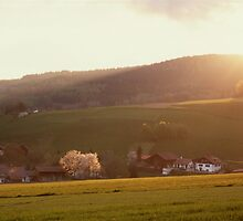 Sunset, village and rolling hills by intensivelight