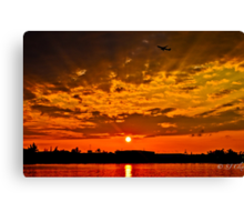Flight travels through the skies when sun goes down Canvas Print