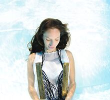 A young woman in white dress floats underwater  by PhotoStock-Isra