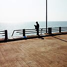 Lonely Man Sitting On Railing By The Ocean by visualspectrum