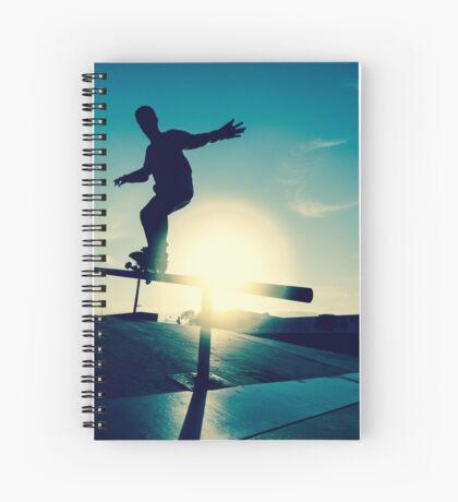 Skateboarder silhouette on a grind Spiral Notebook