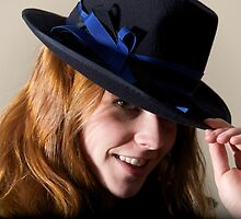 Redhead smiling in black hat touching brim by Nick Dale