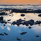 beautiful mellow sunset over rocky beach by morrbyte