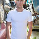 Man standing in auto wrecking yard by Ben Ryan