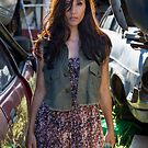 Woman standing amid car wrecks in a salvage yard by Ben Ryan