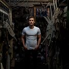 Fit young man standing in a dark industrial workshop by Ben Ryan