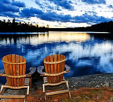 Wooden chairs at sunset on lake shore by Elena Elisseeva