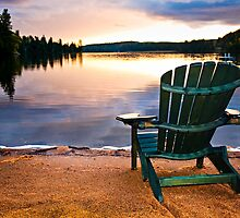 Wooden chair at sunset on beach by Elena Elisseeva