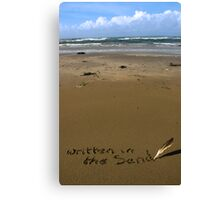 written in the sand on a  beach with feather quill Canvas Print