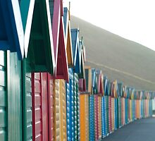 Receding line of colourful beach huts by photoeverywhere