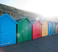 Brightly coloured beach huts by photoeverywhere