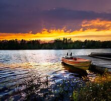 Boat docked on lake at sunset by Elena Elisseeva