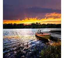 Boat docked on lake at sunset Photographic Print