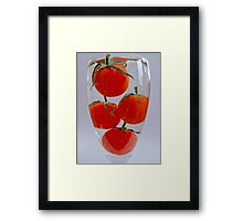 Tomatoes in a glass of water Framed Print